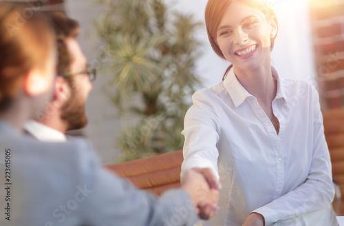 Leinwanddruck Bild business woman greets the employee with a handshake,