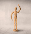 Wooden mannequin posed in front of a greyish background - 223623022