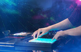 Hand mixing music on dj controller with party club colors around - 223625646