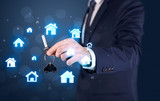 Businessman in suit holding keys with house graphics around and dark background  - 223627461