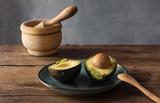 Avocado split in half on a blue plate - 223627647