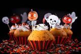 Happy Halloween muffin cupcakes with funny party decorations set against a black background with differential focus and creative lighting. - 223653086