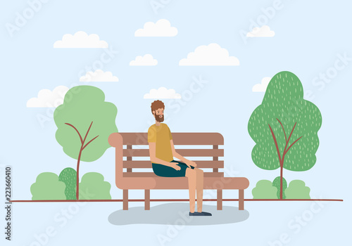 young man sitting on park chair - 223660410
