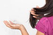 woman worried about Hair loss , young asian female holds loss hair on a white background