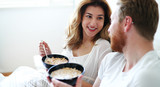 Happy married couple being romantic in bed sharing cereal - 223675092