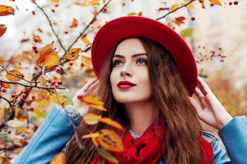 fototapeta na ścianę Close up outdoor portrait of young beautiful happy smiling girl wearing red hat and scarf posing near autumn tree. Model with red lips, long hair. Lady looking up.