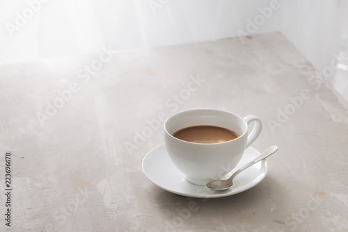 Wall mural White china cup of tea with milk on a plain background