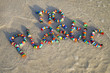 Colorful bottle caps spell out 'no plastic' on a sandy beach as a wave laps around. A reminder for people to take action on pollution - reduce, reuse and recycle.