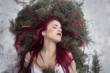Redhead girl lying in the snow dreaming - 223703288