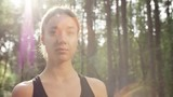 PAN shot of cheerful young woman standing in forest on sunny summer day and looking at camera - 223705838