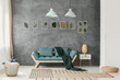 Wicker basket, ottoman and rugs on the floor of an eco style living room interior with mint green decorations and gray wall