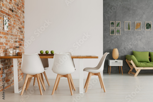 Wooden dining table and chairs by an exposed brick wall in a bright and natural living room interior of a modern loft - 223725640