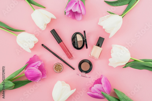 Leinwanddruck Bild Composition with flowers and cosmetics on pink background. Top view. Flat lay. Home feminine desk.