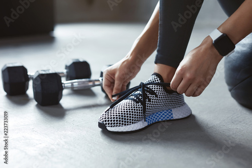 Foto Murales Sports Shoes. Woman Hands Tying Shoelaces On Fashion Sneakers