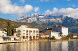 Beautiful Mediterranean landscape on sunny winter day. Montenegro, embankment of Tivat city and snow-capped peaks of Lovcen mountain - 223749099