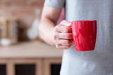 traditional morning hot energizing drink. quick and easy breakfast. man holding tea or instant coffee in a red mug standing in the kitchen. - 223749231