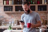 morning habits. man standing in the kitchen having a cup of tea or coffee and checking e-mails or new messages on his mobile phone. - 223749269