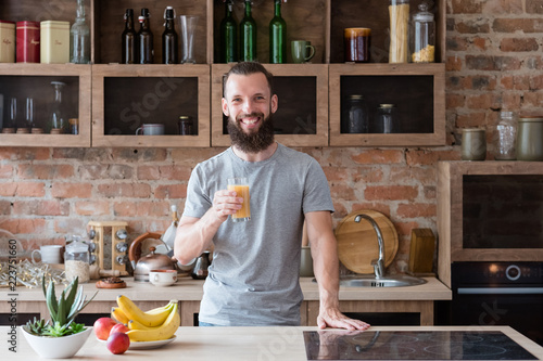 Foto Murales healthy food and balanced nutrition. fresh fruit juice for breakfast. smiling happy bearded man standing in the kitchen holding a glass with vitamin drink.