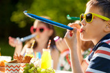 birthday, childhood and celebration concept - close up of happy kids blowing party horns and having fun in summer - 223773493