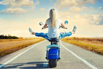 Girl biker riding a motorbike on an asphalt road.