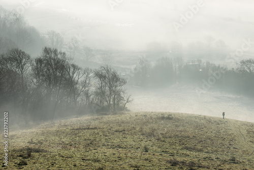Stunning foggy English rural landscape at sunrise in Winter with layers rolling through the fields - 223792202