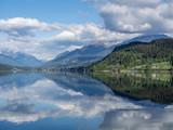 Seelandschaft mit Hügeln, Sonne und weissen Wolken, Österreich - 223818213