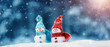 Leinwandbild Motiv little knitted snowmans on soft snow on blue background