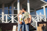 Young happy couple huging and kiss outside with moving boxes at new home - 223839478