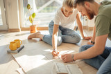 Portrait of happy caucsian couple planning new house design looking at paper - 223840645