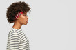 Profile shot of black woman with Afro haircut, thoughtful expression wears headband, round glasses, striped sweater, poses against white background with copy space for your promotional content