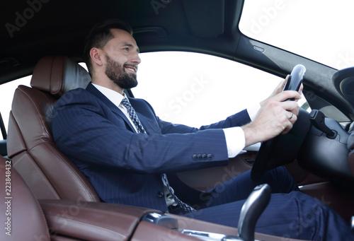 businessman sitting behind the wheel of a car - 223848432