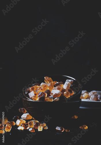 Brown cukieru trzciny cukier w pucharze na czerń stole, selekcyjna ostrość