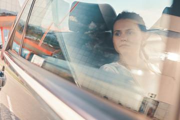 Modern Woman Sitting In Rear Seat Of Car On Road Trip Relaxing