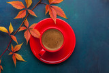 Red cup of black coffee and branch of colorful autumn leaves  (Virginia creeper)  on a dark blue-green wooden table.  Flat lay - 223859624