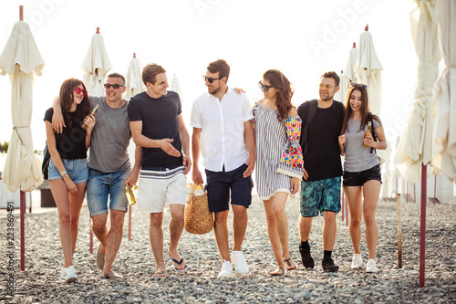 summer, holidays, vacation. group of friends having fun on beach, walking, drink beer, smiling and hugging
