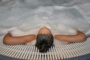 Hidromasaje de mujer joven de espaldas en bañera de burbujas en sesión relajante y de belleza