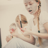 Woman with grey clay mud mask on her face - 223870403