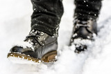 Black boots in snow, person put the step in snow, walking in winter - 223870853