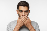Secret, silence concept. Close up portrait of young man in gray t-shirt covering his mouth with hands isolated on grey background - 223872066