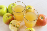 two glasses of juice, Apple juice, whole apples and apples cut in half - 223887628