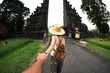 Woman in asian dress and hat holding man by hand travelling Asia