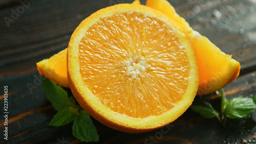 Closeup sliced orange with green leaves on dark wooden background  - 223903635