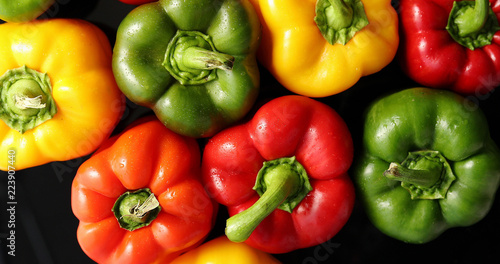 From above view of colorful ripe peppers placed together on black background - 223907440