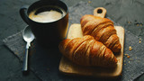 From above view of two fresh croissants and black mug with coffee placed on napkin on gray background of table