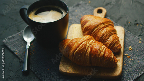 Wall mural From above view of two fresh croissants and black mug with coffee placed on napkin on gray background of table