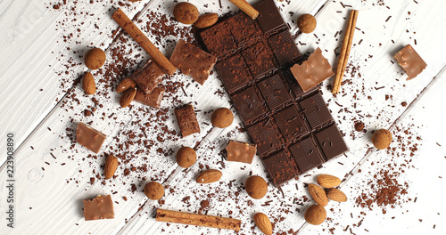From above view of arrangement with bar of dark chocolate on white wooden table with cocoa and nuts and cinnamon sticks