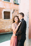 Romantic couple in Venice. Young woman and man in elegant clothes hugging near the venetian canal and ancient buildings. Italy, Europe.