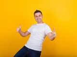 Handsome, cheerful, positive guy in jeans and a white T-shirt on a yellow background - 223920692
