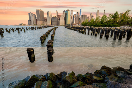 New York skyline and old dock pylons with warm colored clouds in the sky