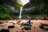 The tourist take a photo waterfall in deep forest with smartphone.